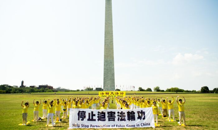 Over one hundred of Falun Gong practitioners are practicing exercises on the grass in front of the Washington Monument to urge the stopping of the CCP's persecution of their spiritual discipline, in Washington, D.C., on July 19, 2020. (Lisa Fan/The Epoch Times)