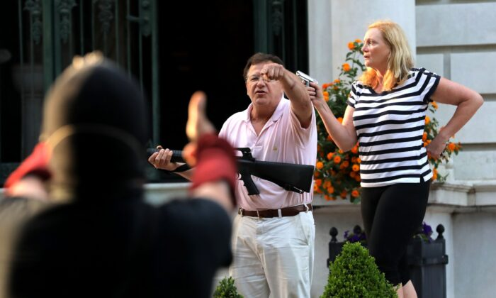 Armed homeowners Mark and Patricia McCloskey, stand in front their house along Portland Place to confront protesters marching to St. Louis Mayor Lyda Krewson's house in the Central West End of St. Louis, Mo., on June 28, 2020. (Laurie Skrivan/St. Louis Post-Dispatch via AP)