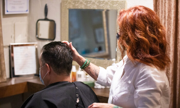 Owner Christine Maniaci gives a customer a haircut at Salon Touche in Redondo Beach, Calif., on July 16, 2020. (John Fredricks/The Epoch Times)