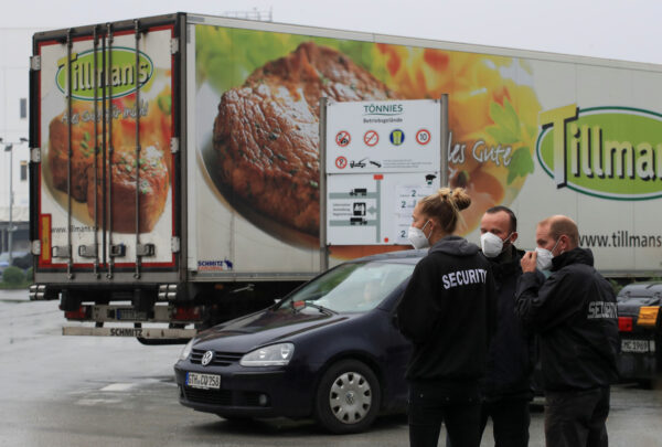 Security personnel stand in front of a meat truck