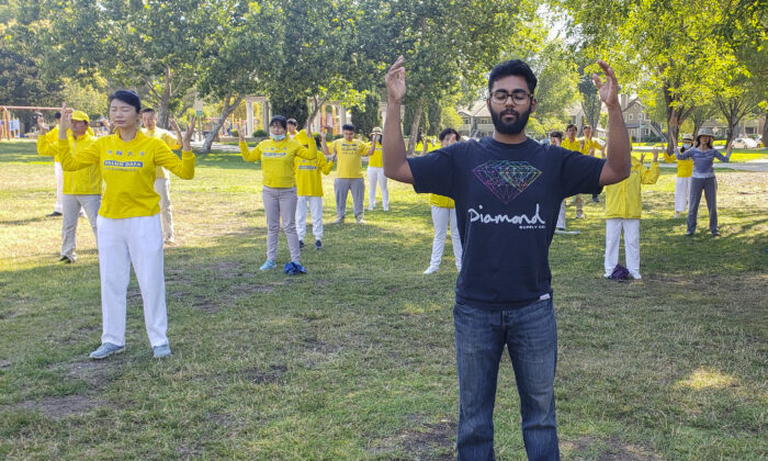 Vijay Kumar medidates with fellow Falun Dafa practitioners at Townsend Park in San Jose on July 18, 2020. (David Lam/The Epoch Times)