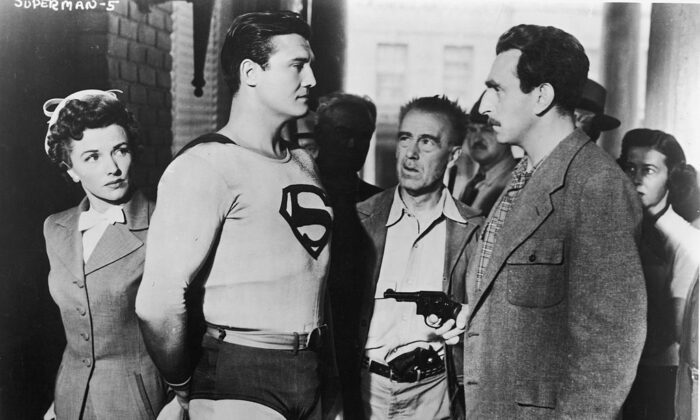 """Actor George Reeves (1914–1959), as Superman, stands in front of actress Phyllis Coates, as Lois Lane, in a still from the television series """"Adventures of Superman,"""" circa 1952. (Hulton Archive/Courtesy of Getty Images)"""