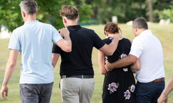 Amelie Lemieux (2nd R), is comforted by family members as she leaves a memorial for her two daughters, Romy and Norah Carpentier, in Levis, Que., on July 13, 2020. (The Canadian Press/Jacques Boissinot)