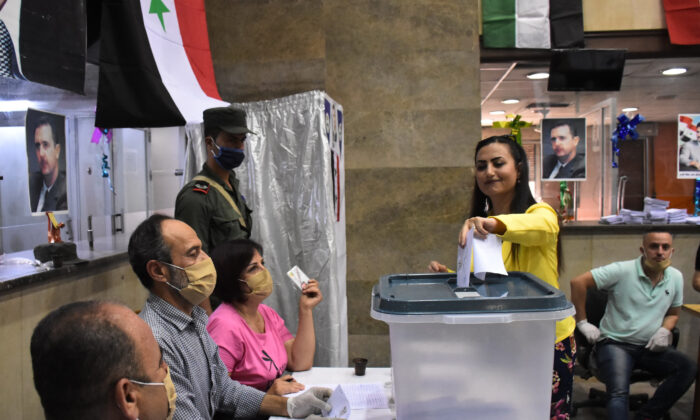 A woman casts her ballot at a voting station in the northern Syrian city of Aleppo on July 19, 2020, during the parliamentary elections. (-/AFP via Getty Images)