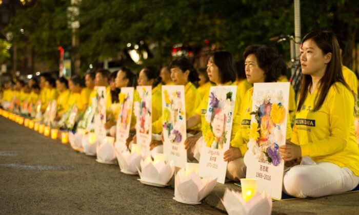 Falun Gong practitioners hold a candlelight vigil in front of the Chinese Consulate in Toronto on July 13, 2019, holding photos of fellow adherents who had died as a result of persecution in China. (Handout)