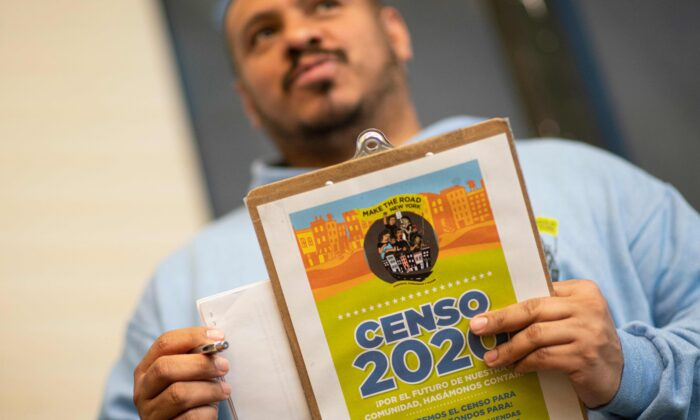 Douglas Carrasquell of the organization Make the Road New York holds documents as he attends a training meeting about National Census in Queens in New York City on March 13, 2020. (Kena Betancur/AFP via Getty Images)