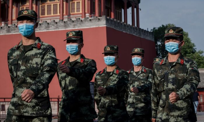 Paramilitary police officers march next to the entrance to the Forbidden City in Beijing on May 22, 2020. (Nicolas Asfouri/AFP via Getty Images)