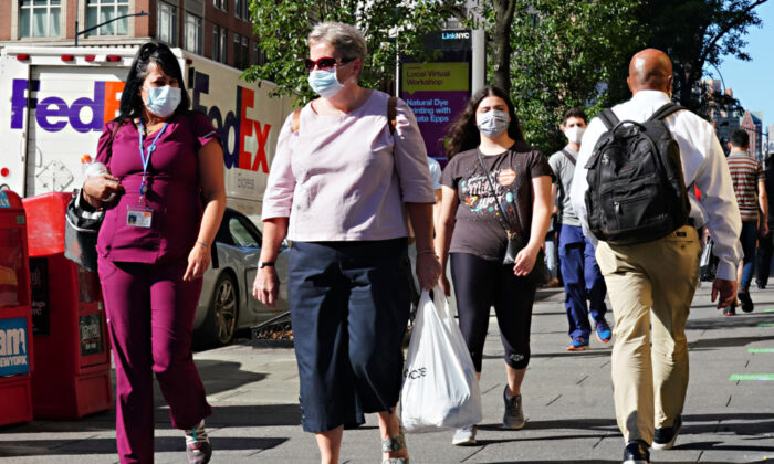 People walk while wearing protective masks as New York City moves into Phase 3 of reopening following restrictions imposed to curb the CCP virus pandemic, on July 14, 2020. (Cindy Ord/Getty Images)