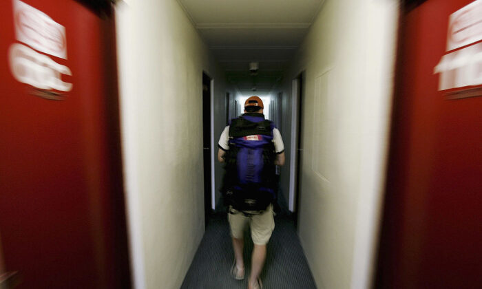 Traveller Craig Weather from Canada walks through a dormitory corridor as he arrives at a backpackers hostel October 14, 2005 in Darwin, Australia. (Ian Waldie/Getty Images)
