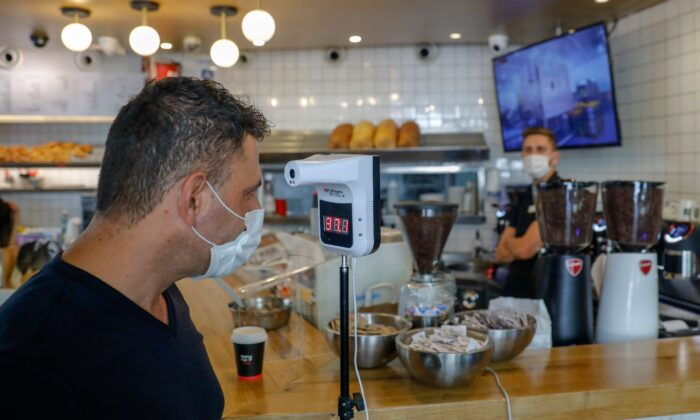A man checks his body temperature as he enters a coffee shop in Jerusalem, amid a surge in coronavirus cases in Israel, on July 17, 2020. (Ahmad Gharabli / AFP via Getty Images)