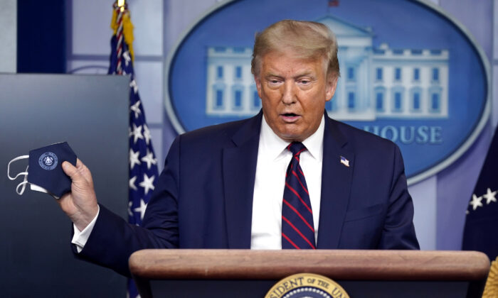 President Donald Trump holds a face mask as he speaks during a news conference at the White House in Washington on July 21, 2020. (Evan Vucci/AP Photo)