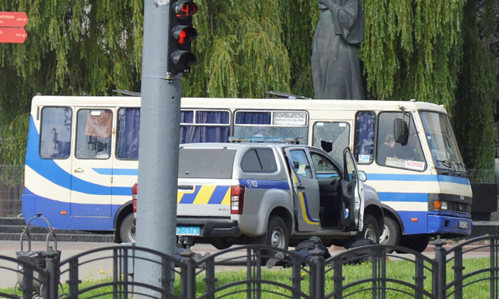 Ukrainian law enforcement officers lie on the ground behind a car near a passenger bus, which was seized by an unidentified person in the city of Lutsk, on July 21, 2020. (Tetiana Hrishyna/Reuters)
