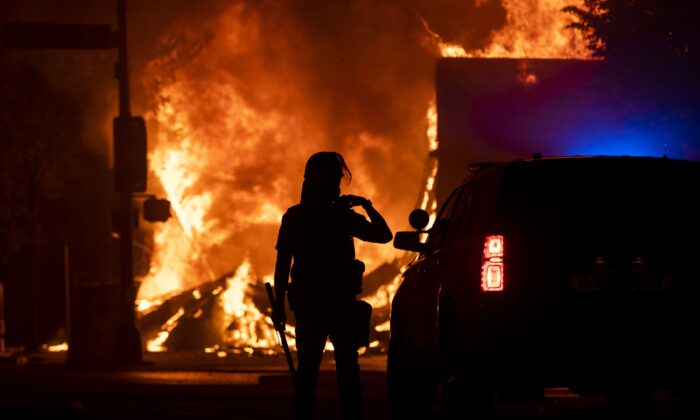 A police officer stands watch as a looted pawn shop burns behind them, in Minneapolis, Minn., on May 28, 2020. (Stephen Maturen/Getty Images)