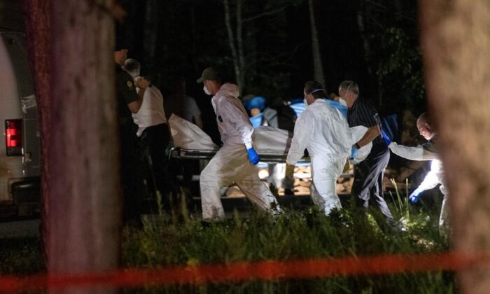 A body believed to be Martin Carpentier is carried by police investigators, Monday, July 20, 2020 in Saint-Apollinaire, Que. (Jacques Boissinot/The Canadian Press)