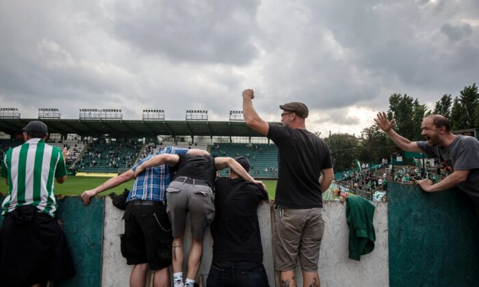 Football fans cheer and stand on ladders as they watch a Czech First League match between Bohemians 1905 and FK Jablonec at Dolicek Stadium in Prague, Czech Republic, on June 14, 2020. (Gabriel Kuchta/Getty Images)