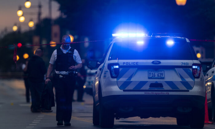 Chicago police investigate the scene of a mass shooting where more then a dozen people were shot in the Gresham neighborhood, on July 21, 2020. (Tyler LaRiviere/Sun-Times/AP)