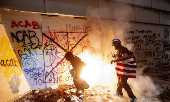 Rioters next to a fire they set at the Mark O. Hatfield United States Courthouse in Portland, Ore., on July 22, 2020. (Noah Berger/AP Photo)