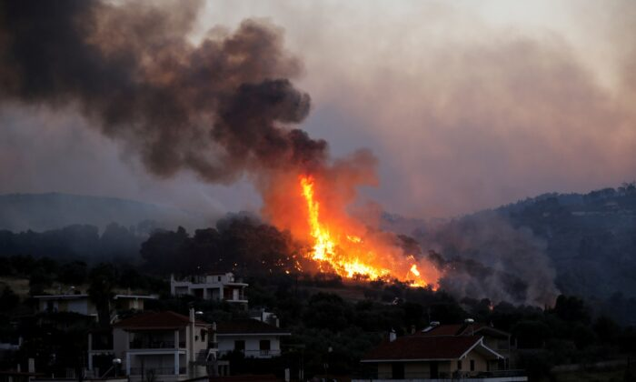 Flames rise as a wildfire burns near the village of Kechries, Greece, on July 22, 2020. (Costas Baltas/Reuters)