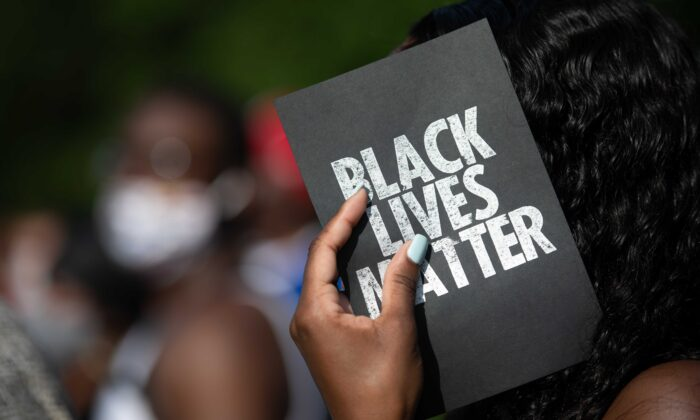 "A demonstrator holds a card that reads ""Black Lives Matter,"" outside of the Glynn County courthouse in Brunswick, Ga., on June 4, 2020. (Sean Rayford/Getty Images)"