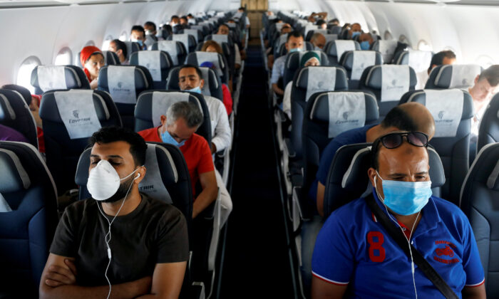 Passengers wearing protective face masks sit on a plane at Sharm el-Sheikh International Airport, following the outbreak of the coronavirus disease (COVID-19), in Sharm el-Sheikh, Egypt, June 20, 2020. (Mohamed Abd El Ghany/Reuters)
