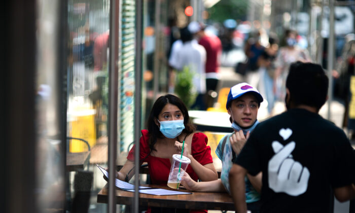 Customers wear protective masks as they order food outside a restaurant in New York City, N.Y., on July 21, 2020. (Jeenah Moon/Getty Images)