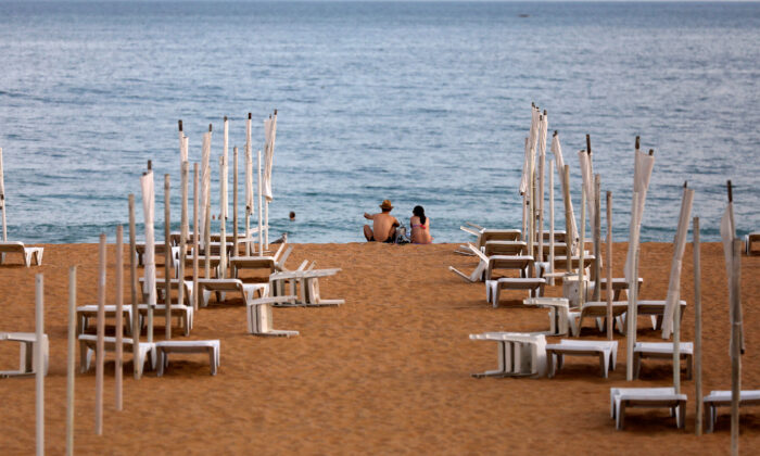 A couple is seen next to empty hammocks during the coronavirus disease (COVID-19) pandemic in downtown Albufeira, Portugal, on July 20, 2020. (Rafael Marchante/Reuters)