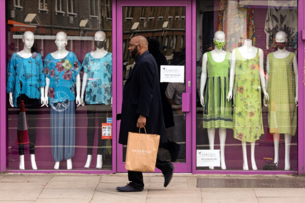 A man walks past a closed retail outlet in London