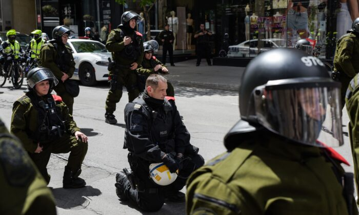 Police officers kneel behind a police line as protesters march in solidarity with protests in the United States over the killing of George Floyd, in Montreal on June 7, 2020. (Martin Oulett-Diotte/AFP via Getty Images)