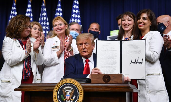 President Donald Trump signs an executive order on lowering drug prices at the White House in Washington on July 24, 2020. (Brendan Smialowski/AFP via Getty Images)
