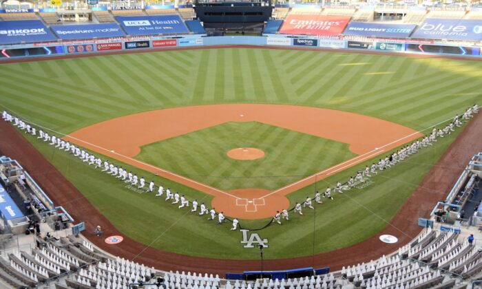 The Los Angeles Dodgers and the San Francisco Giants gather on the field before their game at Dodger Stadium in Los Angeles on July 23, 2020. (Harry How/Getty Images)