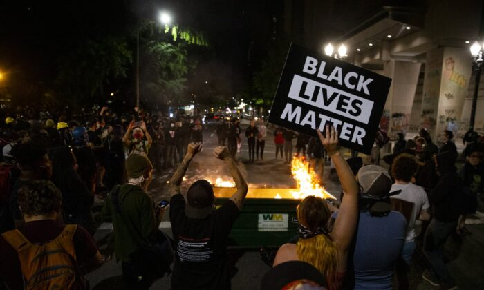 A waste receptacle was moved into the intersection of SW 3rd and Main and its contents set on fire as Portland protesters gathered downtown on July 10, 2020. (Dave Killen/The Oregonian via AP)