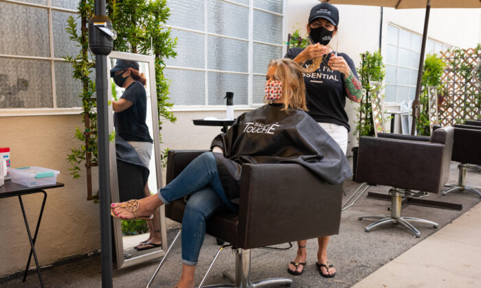 Christina Maniaci cuts a customer's hair at Salon Touché in Redondo Beach, Los Angeles County, on July 22, 2020. (John Fredricks/The Epoch Times)