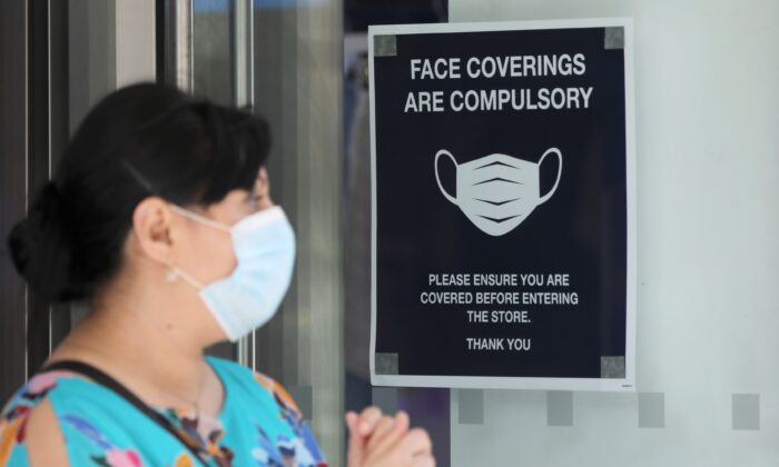 A woman wears a protective mask next to a sign urging to wear face coverings at a store, as the spread of the CCP virus continues, in London, Britain, on July 24, 2020. (Simon Dawson/Reuters)