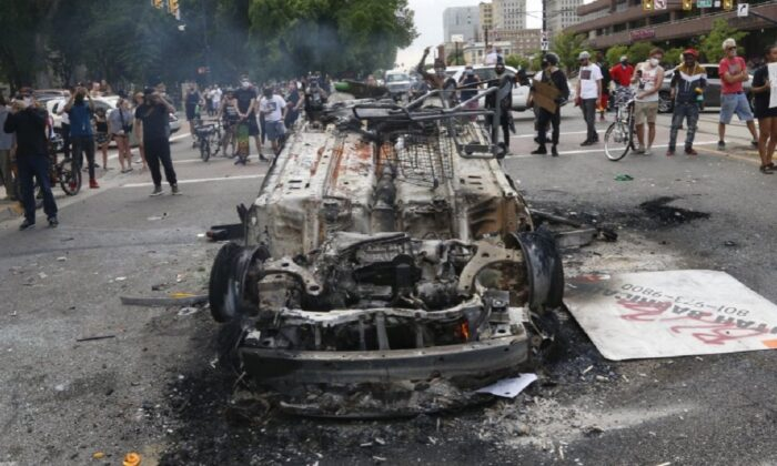 A police vehicle that was overturned and set on fire during riots in Salt Lake City, Utah, is seen on May 30, 2020. (Rick Bowmer/AP Photo)