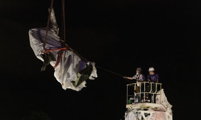 City municipal crews help guide the Christopher Columbus statue in Grant Park as it is removed by a crane in Chicago in the pre-dawn hours of July 24, 2020. (Tyler LaRiviere/Sun-Times/Chicago Sun-Times via AP)