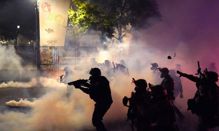 Federal officers deploy tear gas and less-lethal munitions while dispersing a crowd from the Mark O. Hatfield Courthouse in Portland, Ore., on July 24, 2020. (Nathan Howard/Getty Images)