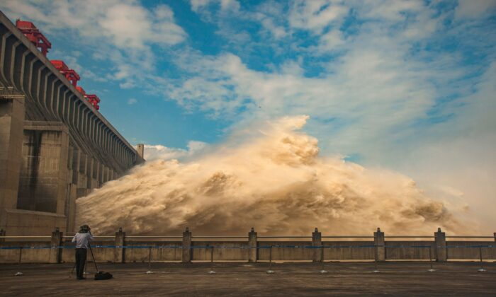 A person takes photos while water is released from the Three Gorges Dam, a gigantic hydropower project on the Yangtze river, to relieve flood pressure in Yichang, central China's Hubei province on July 19, 2020. (STR/AFP via Getty Images)
