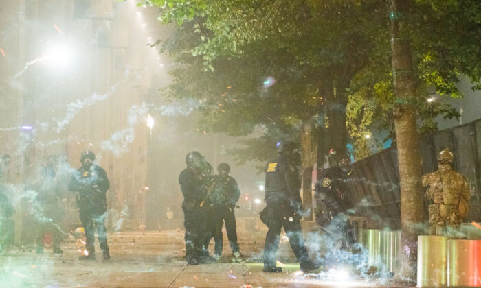 Fireworks go off near federal police guarding the Mark O. Hatfield federal courthouse in downtown Portland as federal officers confront rioters in Portland, Oregon, on July 24, 2020. (Kathryn Elsesser/AFP via Getty Images)