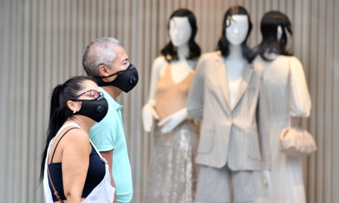 Shoppers wear masks as a precaution against the transmission of the novel coronavirus as they walk past a shop window on Oxford Street in London on July 14, 2020. (Justin Tallis/AFP via Getty Images)