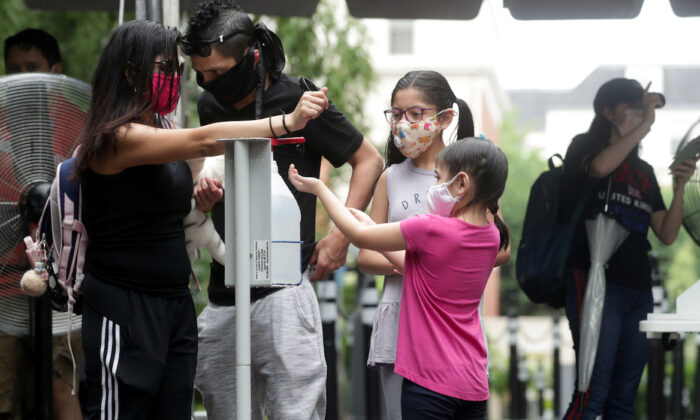 A family use a hand sanitizer station as the National Zoo reopens for socially-distanced patrons for the first time since the start of the COVID-19 outbreak, in Washington on July 24, 2020. (Jonathan Ernst/Reuters)