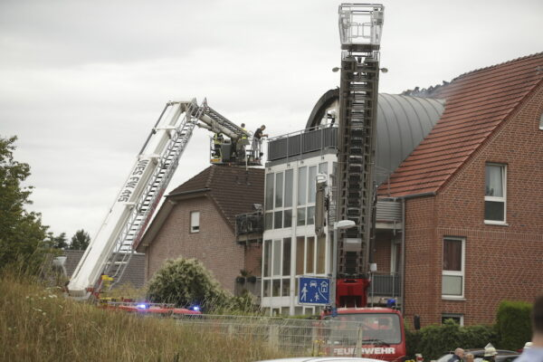 Emergency services attend the scene after a light plane crashed into an apartment building