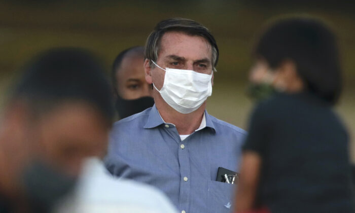 Brazil's President Jair Bolsonaro, who was infected with COVID-19, wears a protective face mask as he stands with supporters during a Brazilian flag retreat ceremony outside his official residence the Alvorada Palace, in Brasilia, Brazil, Fri., July 24, 2020. (Eraldo Peres/AP Photo)