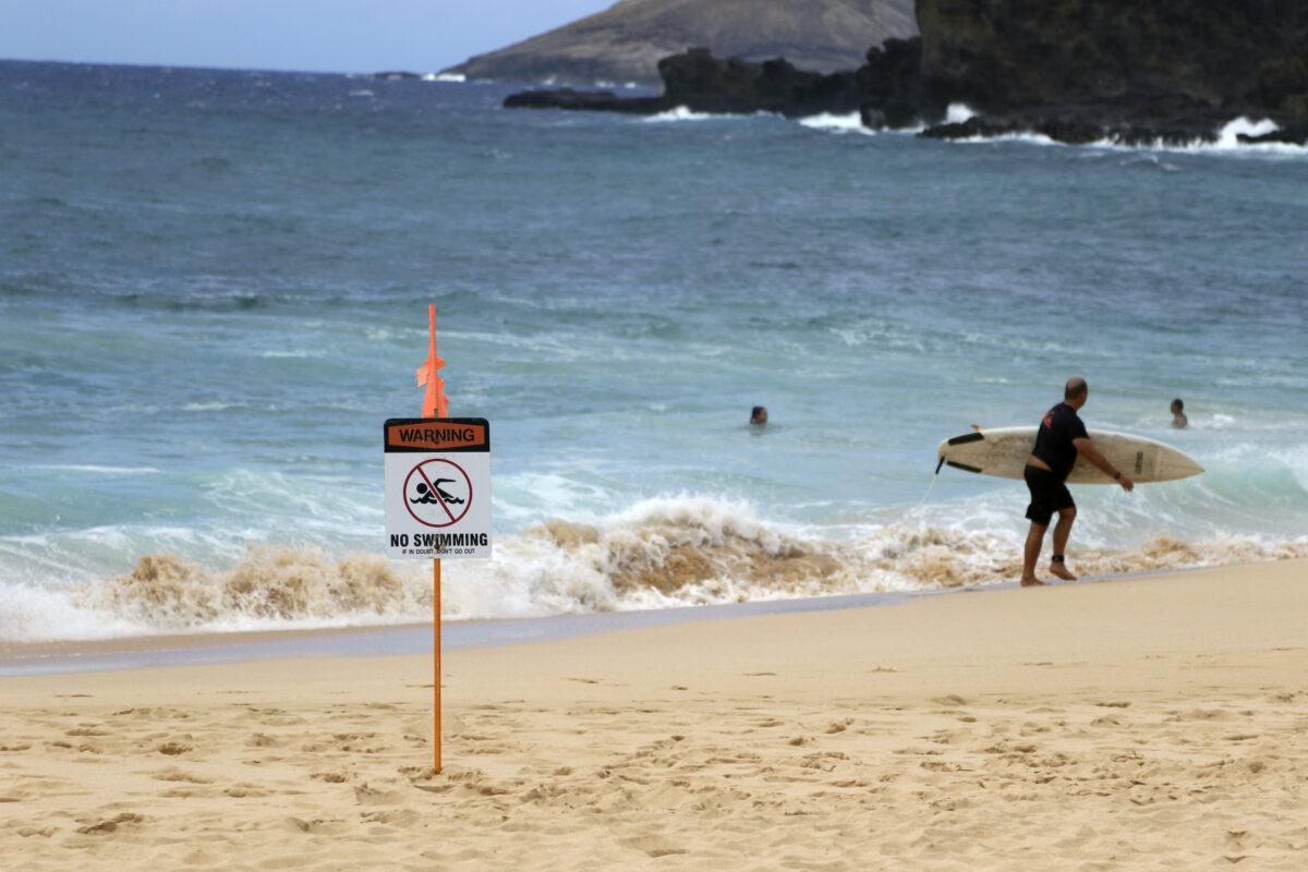 A surfer leaves the water in Honolulu