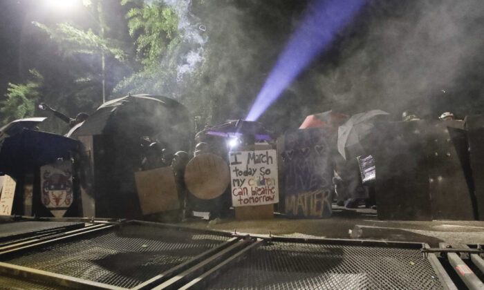 Rioters shield themselves after toppling a fence as federal officers deploy tear gas at the Mark O. Hatfield United States Courthouse in Portland, Ore., on July 26, 2020. (Marcio Jose Sanchez/AP Photo)