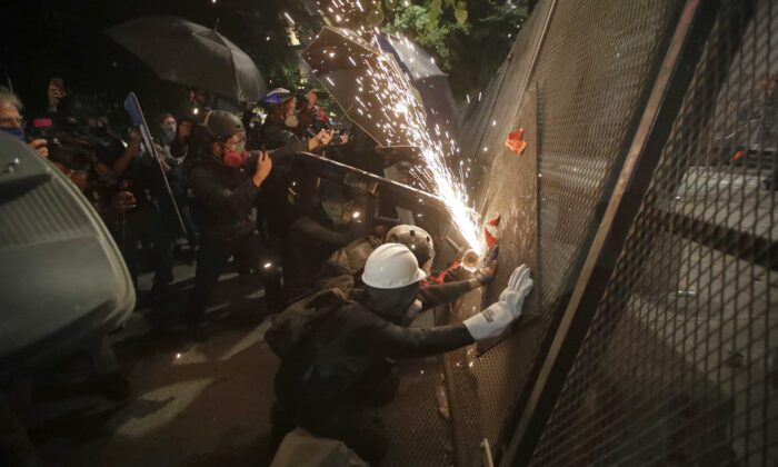 Rioters cut through a steel fence at the Mark O. Hatfield U.S. Courthouse in Portland, Ore., on July 24, 2020. (Marcio Jose Sanchez/AP Photo)