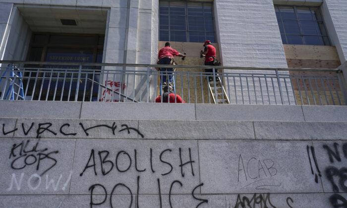 Workers place wooden boards over windows as graffit is shown on walls at the Alameda County Courthouse in Oakland, Calif., on July 26, 2020. (Jeff Chiu/AP Photo)