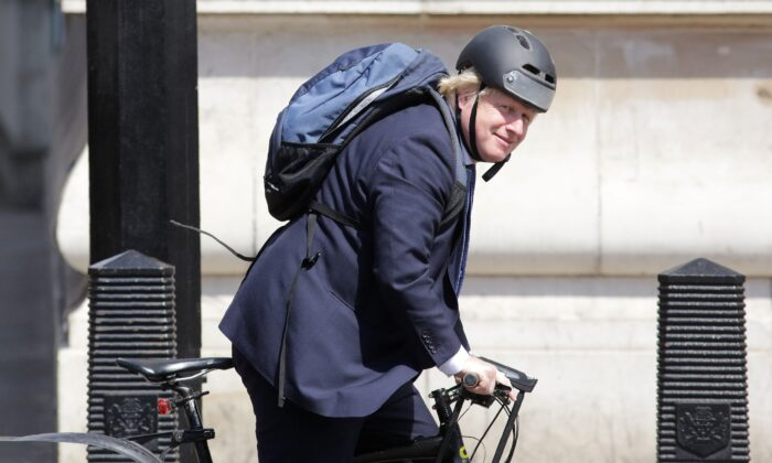 In this file photo, British Prime Minister Boris Johnson rides his bicycle through Westminster in central London on July 6, 2016. (Daniel Leal Olivas/AFP/AFP via Getty Images)