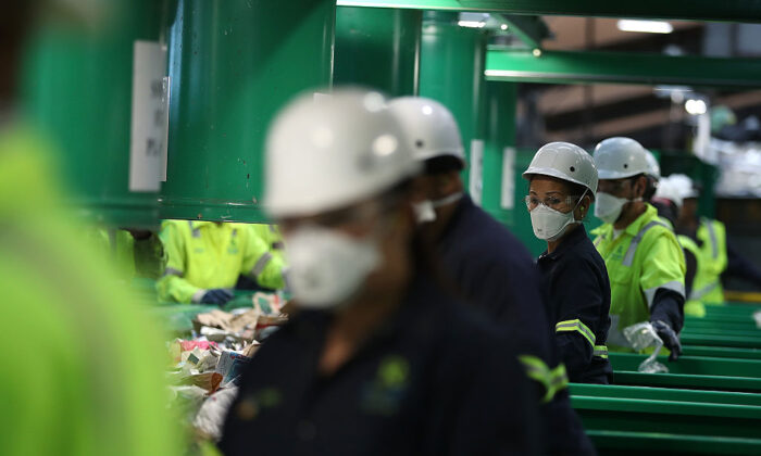 SAN FRANCISCO, CA - NOVEMBER 16:  Workers sort recyclable materials as they pass through a sorting machine at Recology's Recylce Central on November 16, 2016 in San Francisco, California. Recology has installed a state-of-the-art recycling system at their 200,000 square foot Recycle Central facility that is capable of increasing their daily processing of recyclable materials by 170 tons.  (Photo by Justin Sullivan/Getty Images)