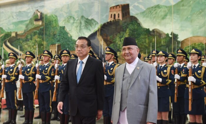 Nepal's Prime Minister K.P. Sharma Oli (center R) reviews a military honour guard with Chinese Premier Li Keqiang during a welcome ceremony at the Great Hall of the People in Beijing on June 21, 2018.  (GREG BAKER/AFP via Getty Images)