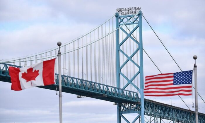 Canadian and American flags fly near the Ambassador Bridge at the Canada-USA border crossing in Windsor, Ont., on March 21, 2020. (Rob Gurdebeke/The Canadian Press)